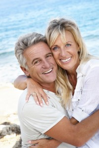 Smiling middle aged couple at the beach
