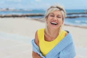 an older woman on the beach smiling