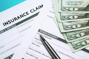an image of money and insurance claims paperwork