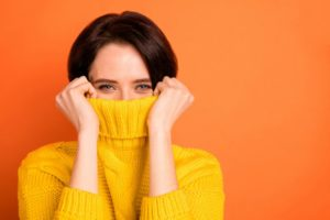 a woman wearing a yellow sweater and using it to hide her gummy smile